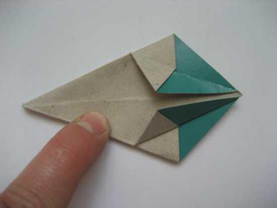 """12. Затем треугольный край согнутых  """"лепестков """" сгибаем к вершине модуля - смотрите фото."""